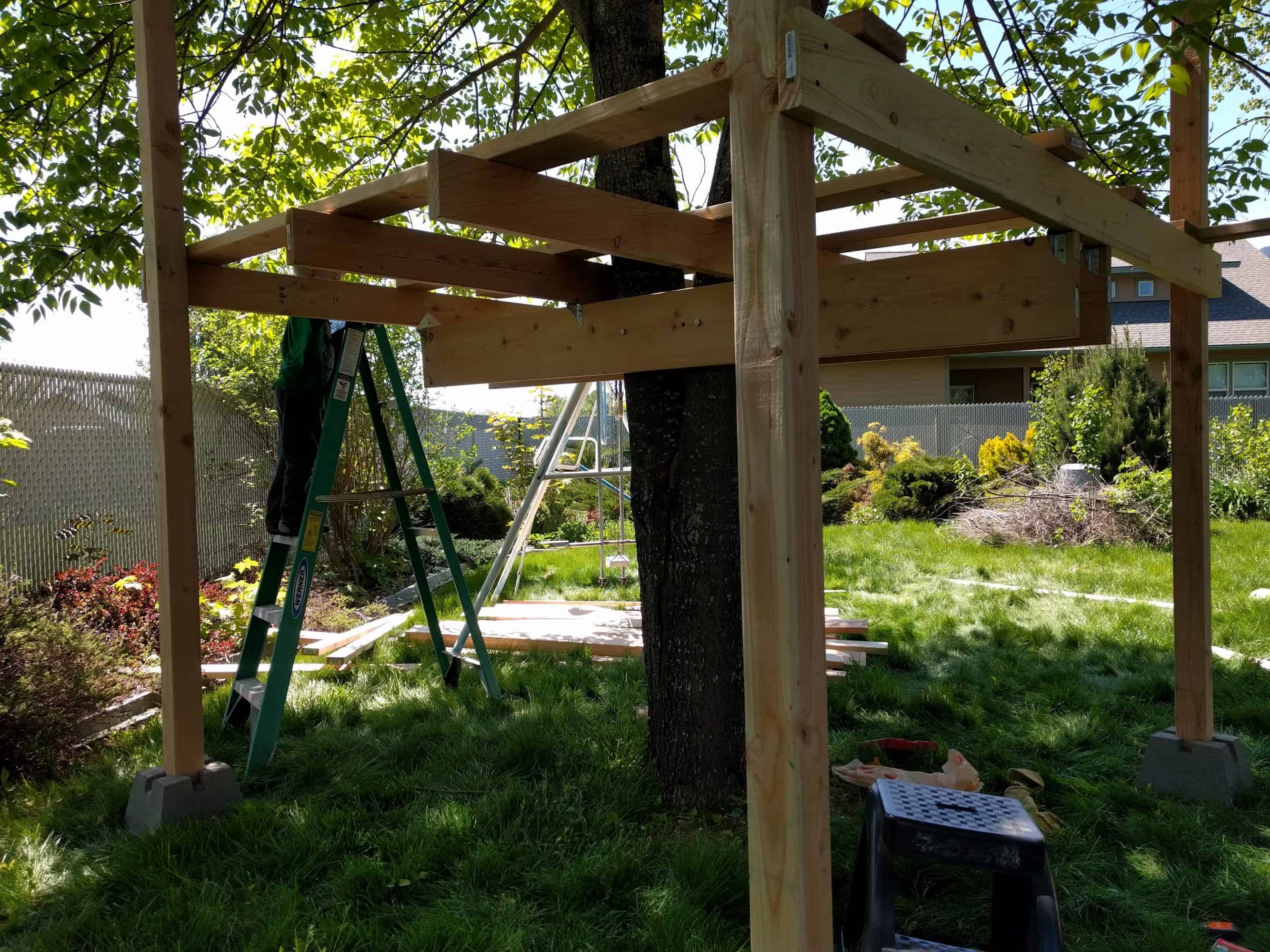 Framing of treefort. Beams, joists, and vertical posts attached at each corner.