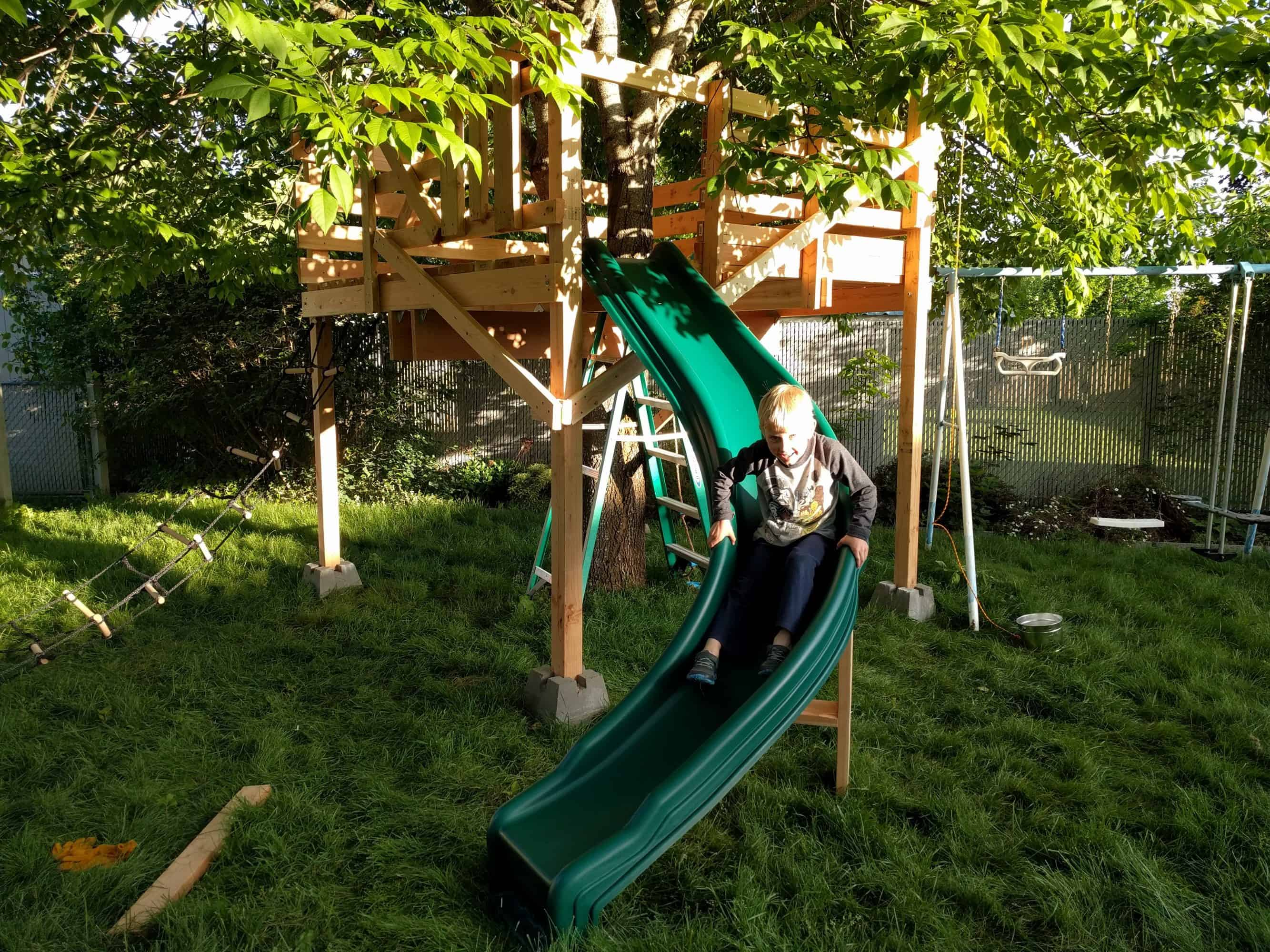 Slide is attached to teehouse. Eli is going down slide.