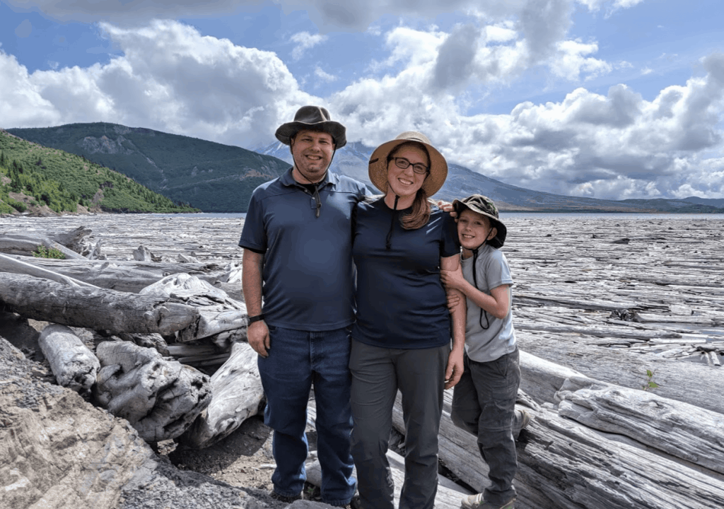 Family in front of floating logs on Spirit Lake